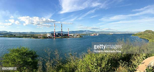 Antonio Maceo power plant with panoramic view of the port channel Red and white chimneys of a factory on the banks of a river and clear blue sky above