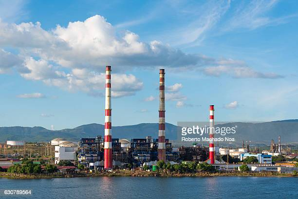 Antonio Maceo thermoelectric The energy producing plant is more than 50 years old Three red and white columns touch the sky with blue building behind...