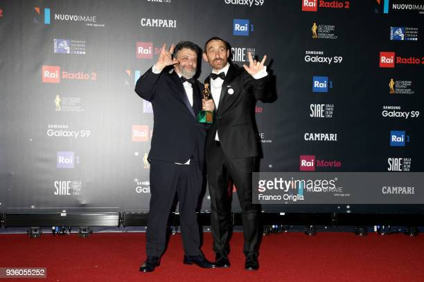 Antonio Manetti and Marco Manetti pose with the Best Movie Award for Ammore e Malavita at the end of the 62nd David Di Donatello awards ceremony on...