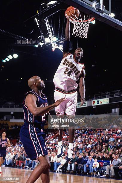 Antonio McDyess of the Denver Nuggets dunks against Scott Burrell of the New Jersey Nets in a game on April 14 1999 at The Pepsi Center in Denver...