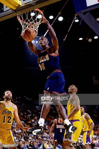 Antonio McDyess of the Denver Nuggets dunks against Vlade Divac of the Los Angeles Lakers in a game on November 3 1995 at The Great Western Forum in...