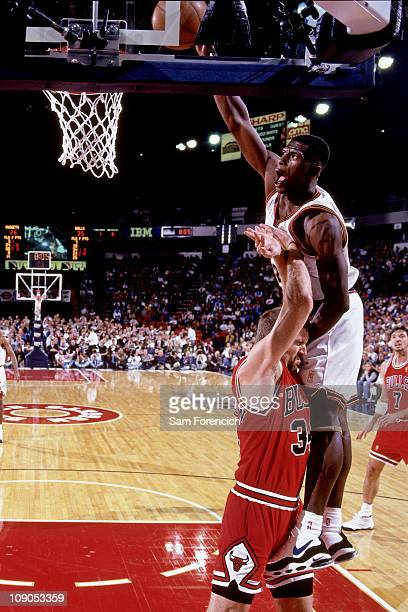 Antonio McDyess of the Denver Nuggets dunks on Bill Wennington of the Chicago Bulls in a game on November 21 1996 at The McNichols Sports Arena in...