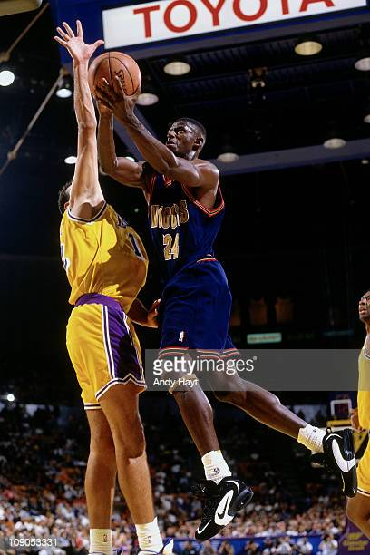 Antonio McDyess of the Denver Nuggets shoots against Vlade Divac of the Los Angeles Lakers in a game on November 3 1995 at The Great Western Forum in...