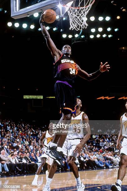 Antonio McDyess of the Phoenix Suns dunks against Erick Dampier of the Golden State Warriors during a game in 1998 at The Arena in Oakland in Oakland...