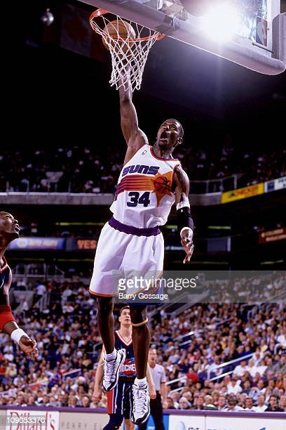 Antonio McDyess of the Phoenix Suns dunks against Hakeem Olajuwon of the Houston Rockets in a game on March 7 1998 at the America West Arena in...