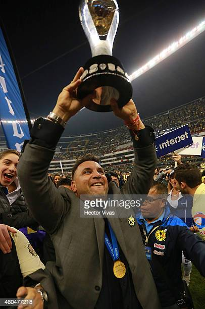 Antonio Mohamed Coach of America celebrates and holds the champions trophy after a Final second leg match between America and Tigres UANL as part of...