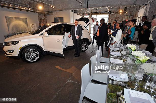 Antonio Molinari left Lincoln MKC Interior Designer speaks with guests during a design discussion and luncheon featuring the all new Lincoln MKC at...