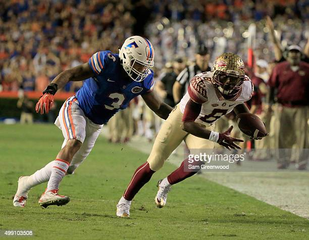 Antonio Morrison of the Florida Gators chses down Kermit Whitfield of the Florida State Seminoles during the game at Ben Hill Griffin Stadium on...
