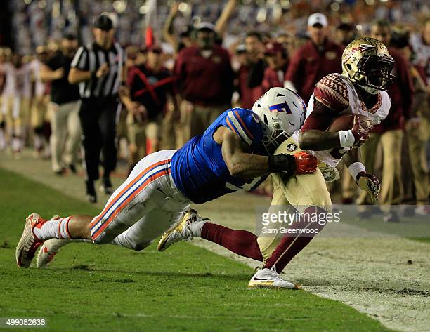 Antonio Morrison of the Florida Gators tackles Kermit Whitfield of the Florida State Seminoles during the game at Ben Hill Griffin Stadium on...