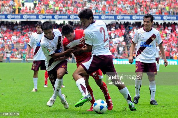 Antonio Naelson of Toluca struggles for the ball with Cesar Moreno and Oswaldo Alanis of Estudiantes during a match as part of the Clausura...
