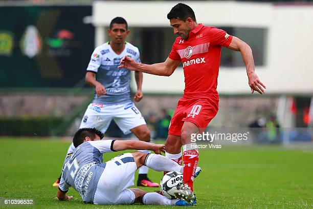 Antonio Naelson of Toluca struggles for the ball with Fernando Navarro of Leon during the 11th round match between Toluca and Leon as part of the...