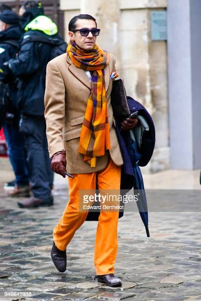 Antonio Nieto wears sunglasses an orange scarf a brown Etro blazer jacket leather gloves orange pants outside Thom Browne during Paris Fashion Week...