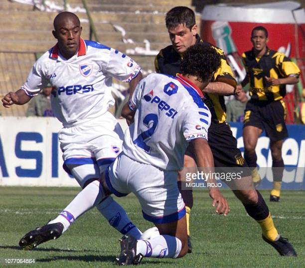 Antonio Pacheco de Penarol deals with a pass between Oscar Morales and Hector Rodriguez National during the second end of the Uruguayan championship...