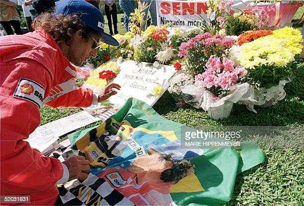 Antonio Paulo Batista displays a flag with the colors of Brazil and a picture of the late Formula One driver Ayrton Senna on the grave of the...