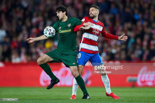 Antonio Puertas of Granada CF competes for the ball with Mikel San Jose of Athletic Club during the Copa del Rey semi-final 2nd leg match between...