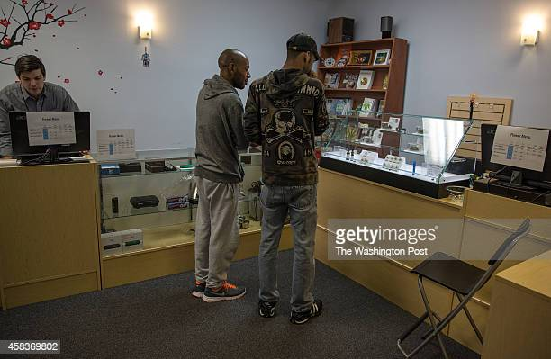 Antonio Randolph and Brian Watson choose what medical marijuana to buy at the dispensary of the Takoma Wellness Center October 10 in Takoma Park DC...