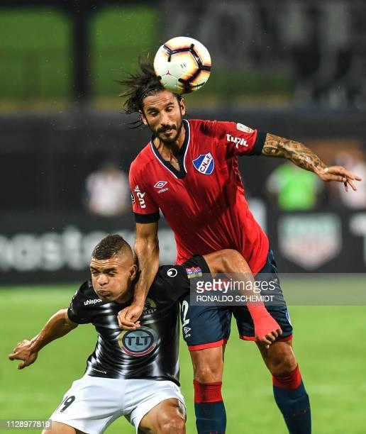 Antonio Romero of Venezuela's Zamora vies for the ball with Uruguay's Nacional Marcos Angeleri during their Copa Libertadores 2019 football match at...