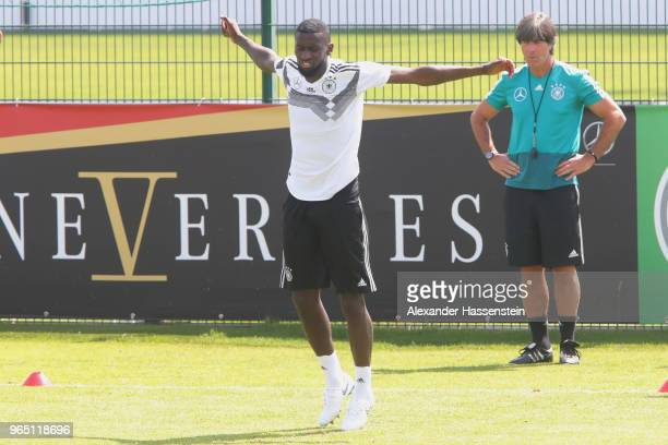 Antonio Ruediger runs next to Joachim Loew head coach of the German national team during a training session of the German national team at...