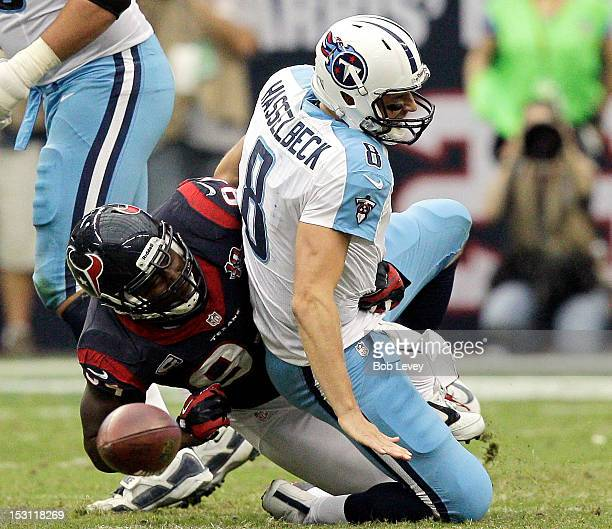Antonio Smith of the Houston Texans forces Matt Hasselbeck of the Tennessee Titans to fumble the ball in the fourth quarter at Reliant Arena at...
