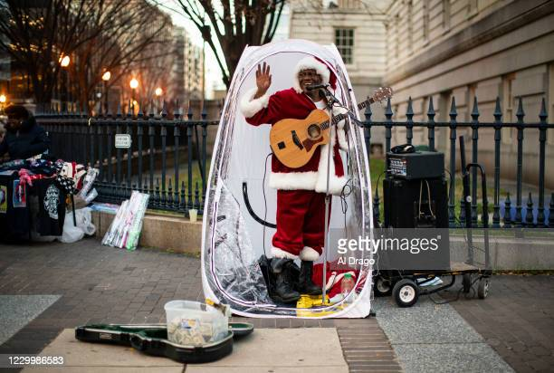 Antonio Tony Covay, dressed as Santa Claus, performs holiday songs, at the Downtown Holiday Market, on December 6, 2020 in Washington, DC. Covay is...