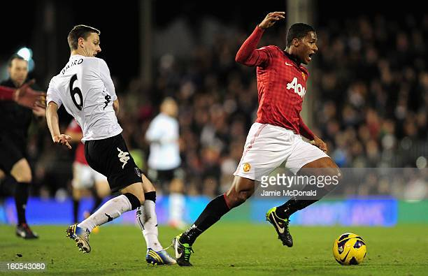 Antonio Valencia of Manchester United falls under the challenge by Chris Baird of Fulham during the Barclays Premier League match between Fulham and...