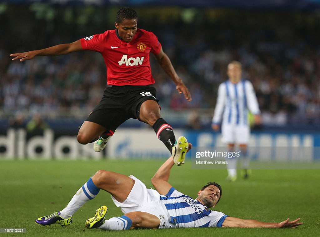 Antonio Valencia of Manchester United in action with Alberto de la Bella of Real Sociedad during the UEFA Champions League Group A match between Real Sociedad and Manchester United at Estadio Anoeta on November 5, 2013 in San Sebastian, Spain.