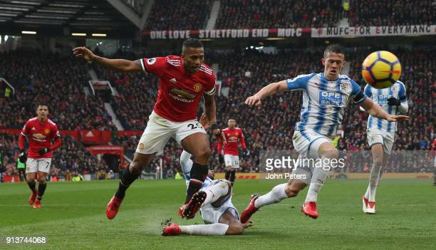 Antonio Valencia of Manchester United in action with Terence Kongolo and Jonathan Hogg of Huddersfield Town during the Premier League match between...