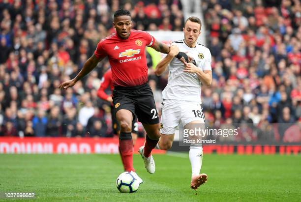 Antonio Valencia of Manchester United is challenged by Diogo Jota of Wolverhampton Wanderers during the Premier League match between Manchester...