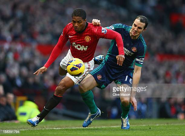 Antonio Valencia of Manchester United is challenged by John O'Shea of Sunderland during the Barclays Premier League match between Manchester United...