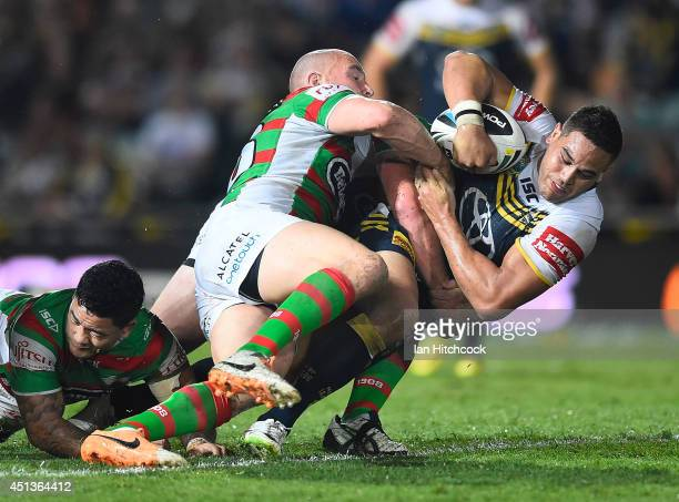 Antonio Winterstein of the Cowboys is tackled by Ben Lowe and Isaac Luke of the Rabbitohs during the round 16 NRL match between the North Queensland...