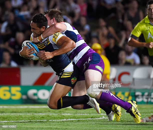 Antonio Winterstein of the Cowboys is tackled by Tim Glasby of the Storm during the round four NRL match between the North Queensland Cowboys and the...