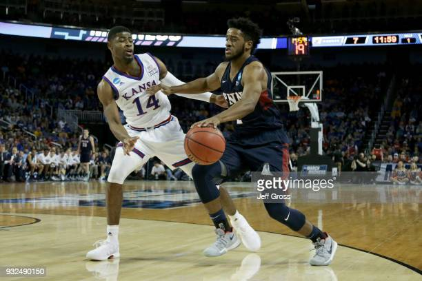Antonio Woods of the Pennsylvania Quakers dribbles the ball while being guarded by Malik Newman of the Kansas Jayhawks in the first half during the...