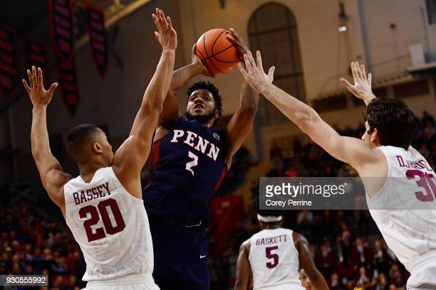 Antonio Woods of the Pennsylvania Quakers shoots the ball between Justin Bassey and Danilo Djuricic of the Harvard Crimson during the second half of...
