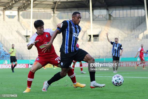 Anton-Leander Donkor of SV Waldhof Mannheim is challenged by Kwon Chang-Hoon of SC Freiburg during the DFB Cup first round match between SV Waldhof...