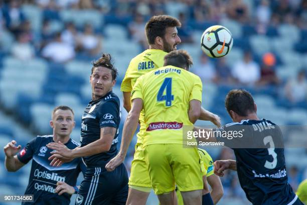 Antony Golec of the Central Coast Mariners heads the ball in front of Jake McGing of the Central Coast Mariners Mark Milligan of Melbourne Victory...