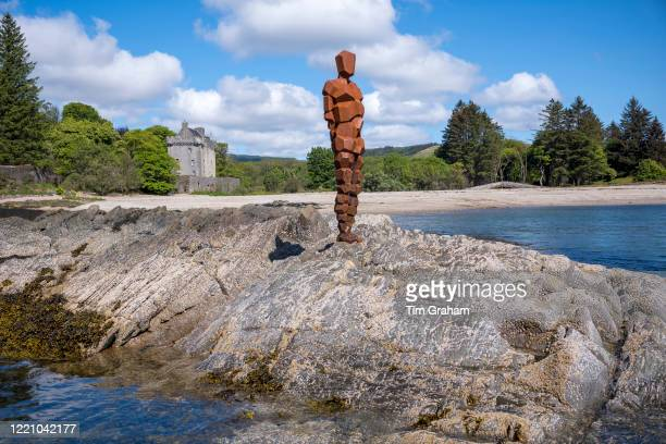 Antony Gormley sculpture GRIP of an abstract human form looking out over Saddell Bay, Kilbrannan Sound to Arran, Saddell Castle in background in...