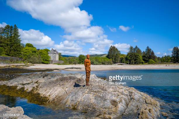 Antony Gormley sculpture GRIP of an abstract human form looking out over Saddell Bay Kilbrannan Sound to Arran Saddell Castle in background in...