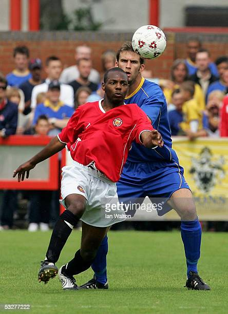 Antony Howard of AFC Wimbledon tries to tackle Adie Orr of FC United of Manchester during the preseason friendly match between AFC Wimbledon and FC...
