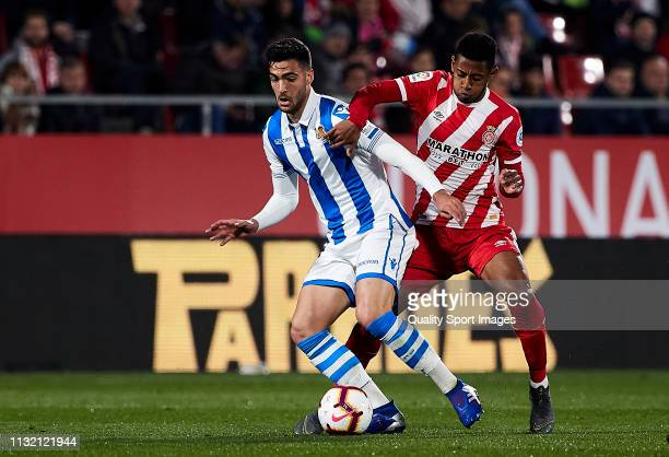 Antony Lozano of Girona FC competes for the ball with Mikel Merino of Real Sociedad during the La Liga match between Girona FC and Real Sociedad at...