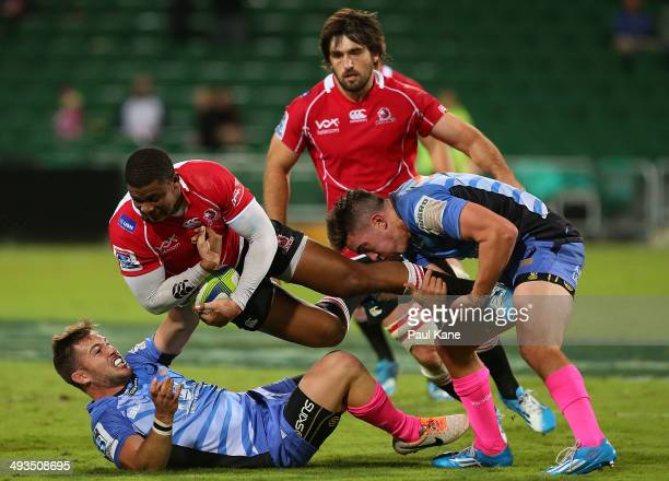 Antony Volmink of the Lions is tackled by Zack Holmes and Luke Burton of the Force during the round 15 Super Rugby match between the Western Force...