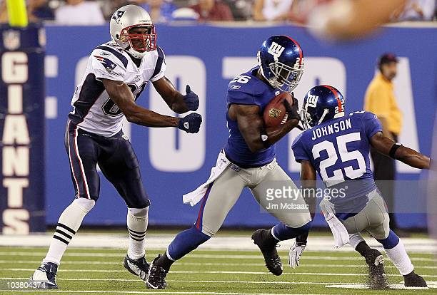 Antrel Rolle of the New York Giants intercepts a pass intended for Randy Moss of the New England Patriots during the first quarter on September 2,...