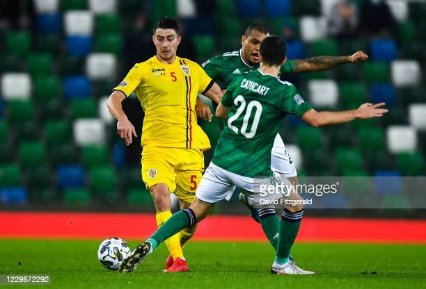 Antrim , United Kingdom - 18 November 2020; Ionu Nedelcearu of Romania in action against Craig Cathcart and Josh Magennis of Northern Ireland during...