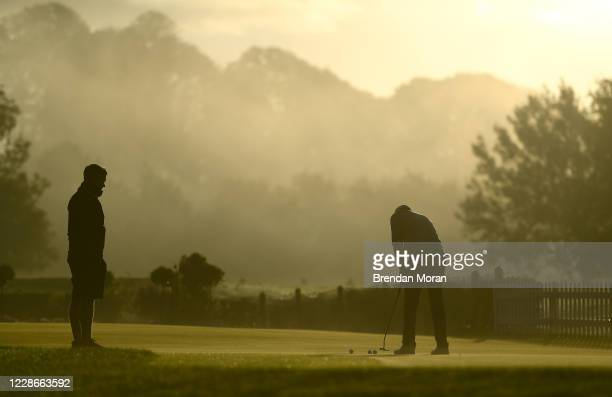 Antrim United Kingdom 23 September 2020 Jason Scrivener of Australia practices on the putting green watched by his caddie Charlie George ahead of a...