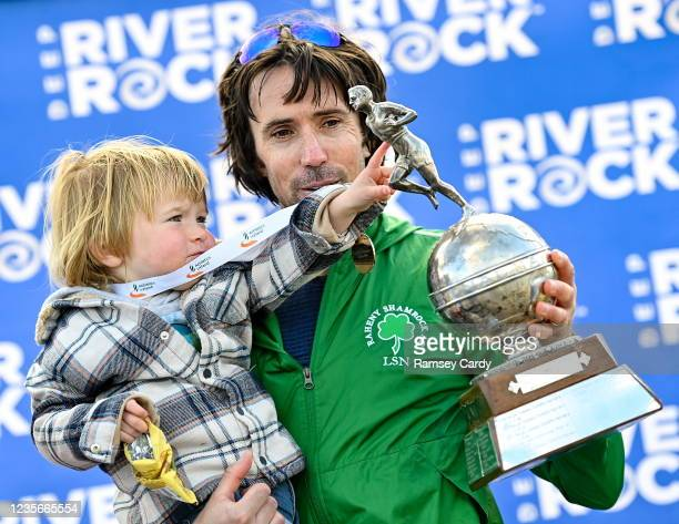 Antrim , United Kingdom - 3 October 2021; Mick Clohisey of Raheny Shamrock AC, Dublin, celebrates with his son Paul, age 2, and his trophy after...