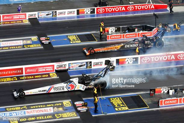 Antron Brown Don Schumacher Racing NHRA Top Fuel Dragster and Clay Millican NHRA Top Fuel Dragster do burnouts during the 19th Annual DENSO Spark...