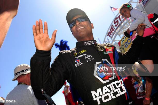 Antron Brown Don Schumacher Racing NHRA Top Fuel Dragster highfives fans during prerace festivities for the NHRA Denso Spark Plugs Four Wide...