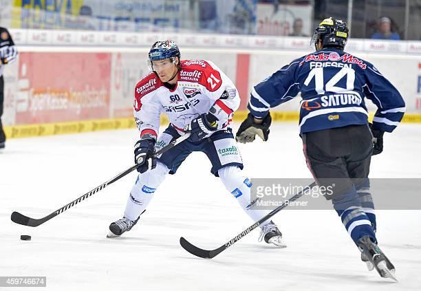 Antti Miettinen of the Eisbaeren Berlin handles the puck against Dustin Friesen of ERC Ingolstadt during the game between ERC Ingolstadt and...