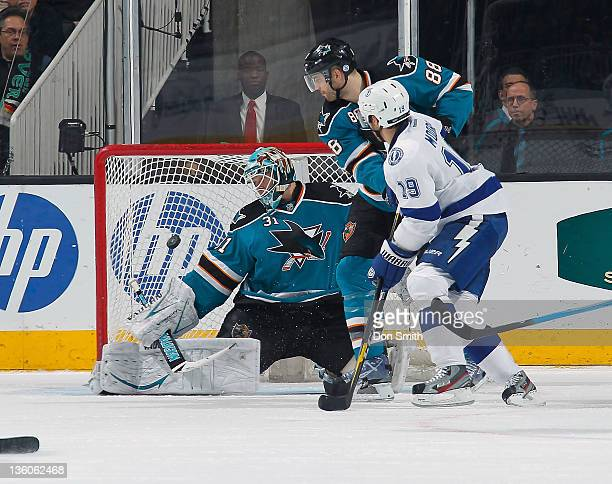 Antti Niemi and Brent Burns of the San Jose Sharks watch as Dominic Moore of the Tampa Bay Lightening scores a goal at HP Pavilion on December 21...