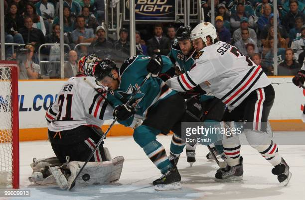 Antti Niemi and Brent Seabrook of the Chicago Blackhawks defend the net against Joe Pavelski and Ryane Clowe of the San Jose Sharks in Game One of...