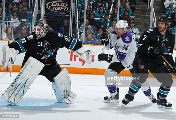 Antti Niemi and Niclas Wallin of the San Jose Sharks protect the net against Justin Williams of the Los Angeles Kings in Game 1 of the Western...